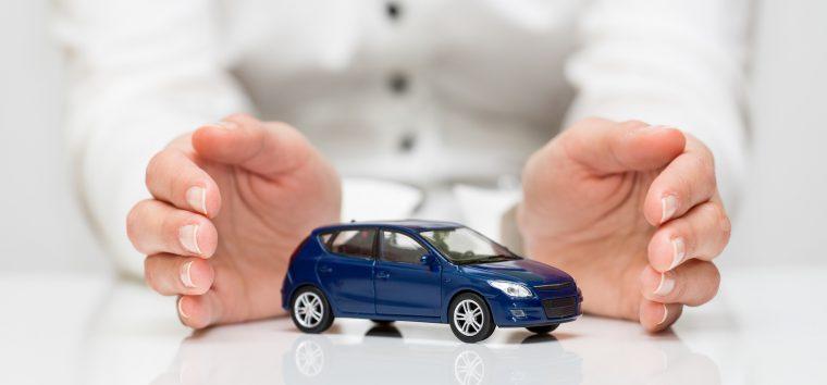 Modrý model auta medzi dlaňami